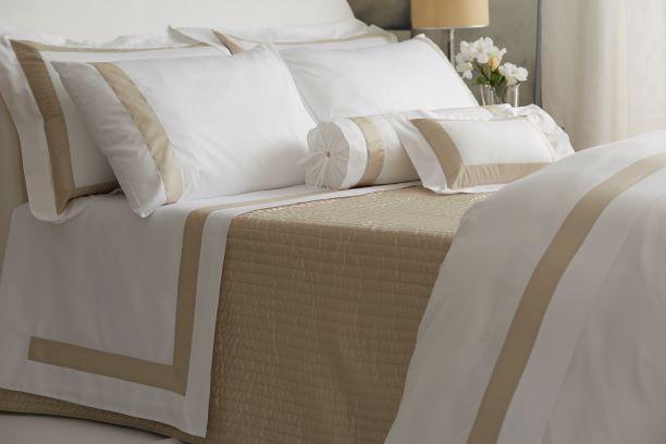 Luxuriöse Bettwäsche in einem Mix aus weiß und beige, mit Kissen in unterschiedlichen Größen
