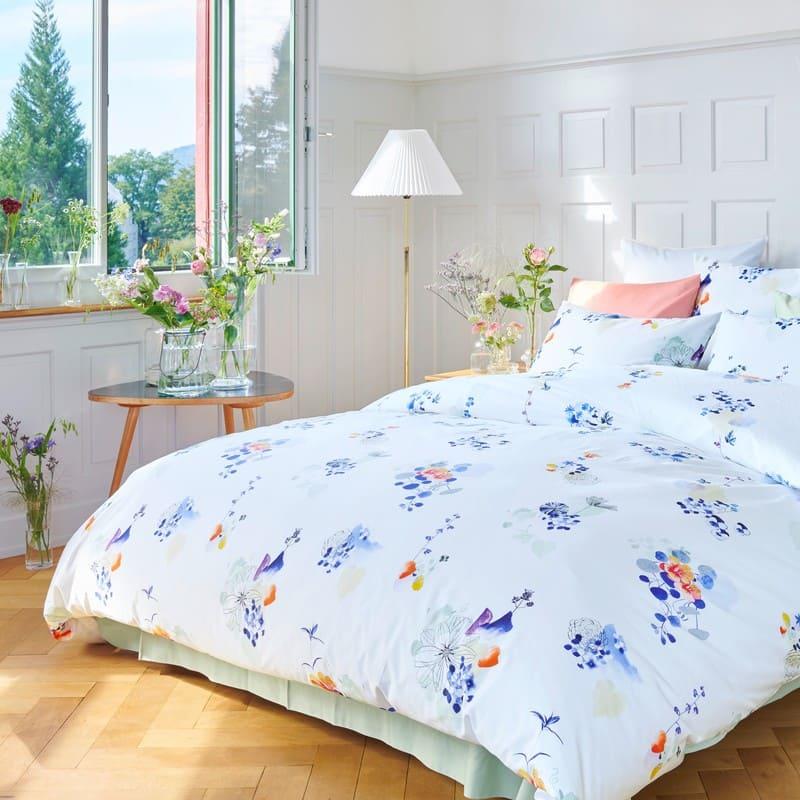 Bettwäsche von Christian Fischbacher mit Blumen in einem hellen Zimmer